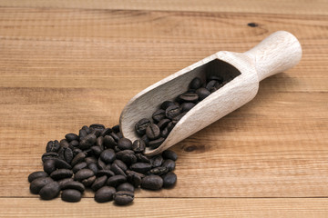 Coffee beans with wooden spoon on wooden table