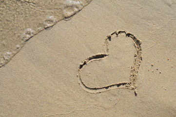 Heart drawn on the sand of beach with sea foam and wave