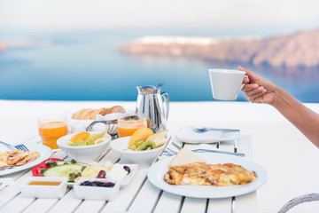 Wall Mural - Morning person drinking coffee cup at breakfast table with mediterranean sea view. Woman eating at restaurant outside terrace patio on Santorini, Greece, Europe destination summer vacation.
