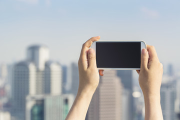 Person holding a smartphone on an urban background