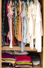 Many colorful clothes in wardrobe