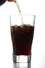 pouring brown soda into glass