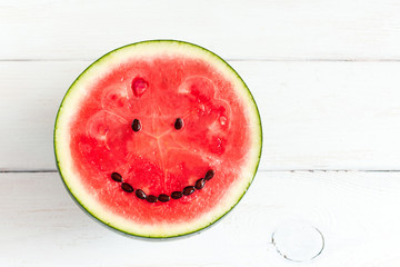 watermelon with smile on white wooden background