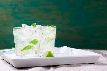 Non alcohol cold mojito cocktail with fresh lime, mint and crushed ice on a white plate on a vintage wooden background, closeup, horizontal with place for text