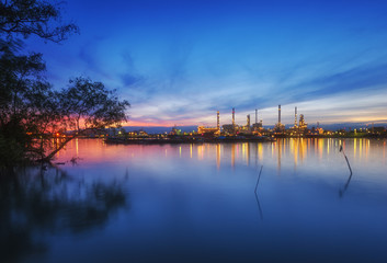 Oil Refinery with blue sky in early morning in Bangkok, Thailand. Concept of Power and Fuel, heavy industry and environment.