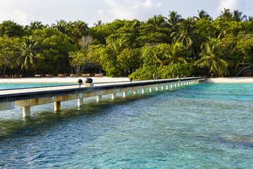 jetty to a little tropical island in the turquoise indian ocean, maldives, way to a travel destination