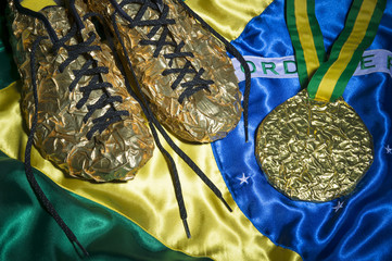 Golden running shoes resting with gold medal on shiny Brazilian flag still life