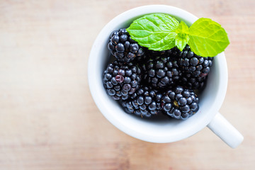 Top view of single cap filled with fresh blackberries and mint.