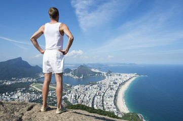 Athlete in vintage white uniform standing at an overlook view of the Rio de Janeiro Brazil skyline