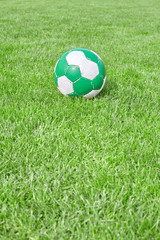 Soccer ball on green grass, space for text.