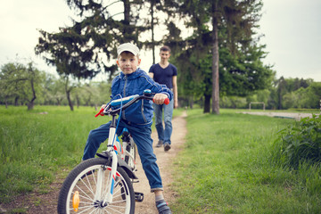Small boy riding a bike together with his father