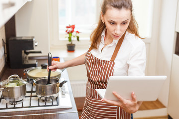 Young woman trying cooking with recipe from laptop