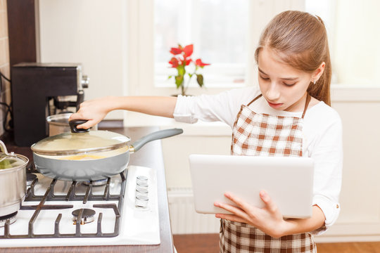 Small teenage girl cooking on cooker with laptop
