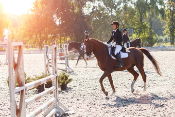 Young girl riding horse in equestrian competition Papier Peint