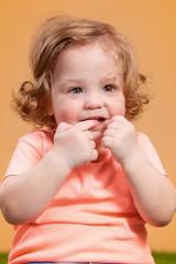 One cute baby girl on orange background