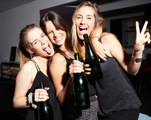 Three girls partying with bottles of wine