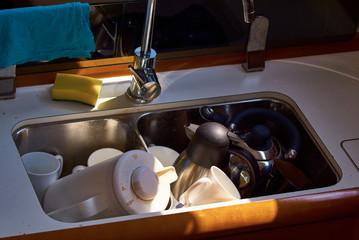 Spüle unter Deck auf einer Segelyacht mit Kaffeekanne und Schwamm
