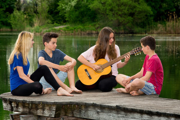 Jugendliche musizieren daußen am See - Gitarre spielen