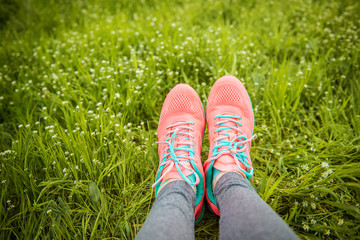 close-up of women's running shoes on the green grass. sport lifestyle concept
