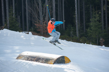 Male skier flying over a hurdle in winter day with forest of firs and ski lifts in background at a winter resort. Bukovel, Ukraine