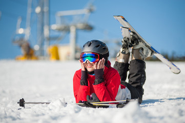 Happy woman skier wearing ski goggles lying with skis on snowy at mountain top and looking away in sunny day with ski lifts and blue sky in background. Bukovel, Ukraine