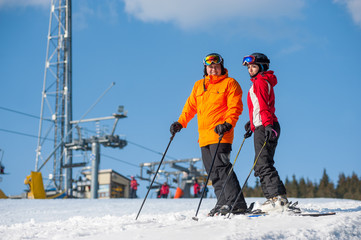 Couple holding skis standing together at a winter resort with ski lifts and blue sky in background. Man is wearing orange jacket, female in red jacket, both is wearing helmet and goggles.