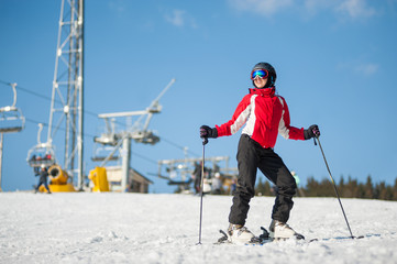 Woman wearing helmet, red jacket and ski goggles standing with skis on mountain top at a winter resort in sunny day with ski lifts and blue sky in background. Bukovel, Ukraine