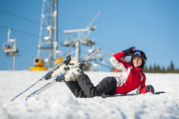 Female raising her ski glasses and looking away, lying with skis on snowy at mountain top in sunny day with ski lifts and blue sky in background.