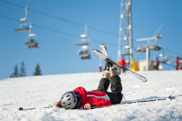 Skier lying face in the snow at mountain top in sunny day with ski lifts and blue sky in background