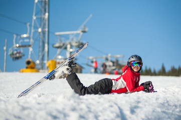 Portrait of female skier lying with skis on snowy at mountain top in sunny day with ski lifts and blue sky in background. Bukovel, Ukraine. Carpathian mountains