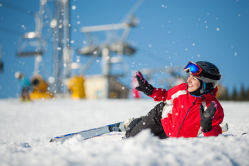 Smiling skier lying with skis on snowy at mountain top and throws snow in sunny day, having fun at a winter resort, ski lifts and blue sky in background. Close-up. Carpathian mountains