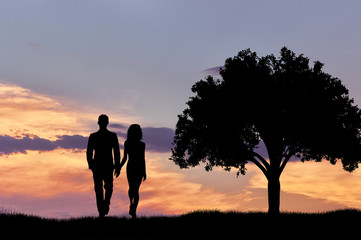 Silhouette of a couple walking at sunset near a tree