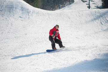 Snowboarder rides over fresh snow after jumping on the slope in winter, extreme sport