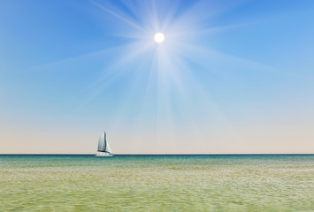 Sunny sky against the backdrop of the sea with a sailboat