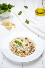 Traditional Italian spaghetti pasta with mushrooms and parmesan cheese, basil. Restaurant menu meal in white dish.