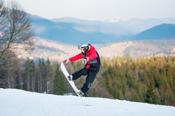 Man standing on his snowboard and taking his for the edge on top of a mountain against the backdrop of mountains, hills and forests in the distance.