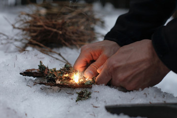 Man lighting a fire in a dark winter forest, preparing for an overnight sleep in nature, warming himself with DIY fire. Adventure, scouting, survival concept. .