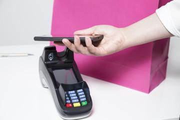Frau bezahlt mit Smartphone im Geschäft