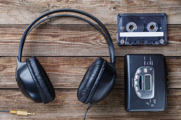 Headphones, player and retro compact cassette over wooden background. Top view