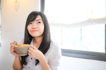 Asian woman drinking coffee and hold cup near window
