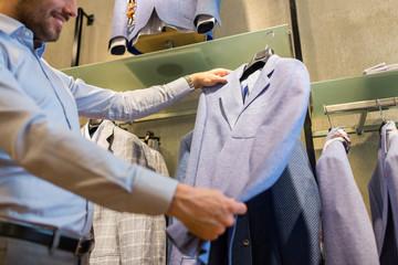 close up of man choosing jacket at clothing store