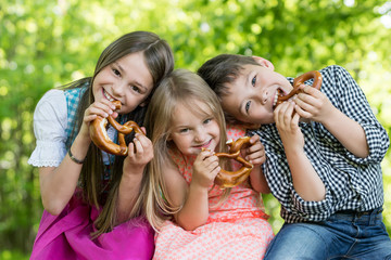 Drei Kinder beissen genussvoll in eine Breze