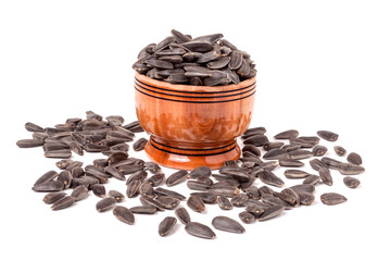 sunflower seeds spill out of wooden barrels on white background
