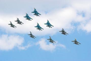 Группа из многофункциональных истребителей-бомбардировщиков Су-34, многоцелевых всепогодных истребителей Су-27 и многоцелевых сверхманёвренных истребителей Су-35с в небе