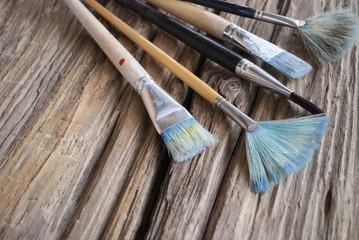Gebrauchte Pinsel in verschiedenen Stärken auf Holz / Treibholz Hintergrund, Textfreiraum