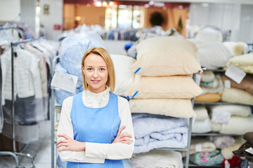 Portrait of a girl worker in a warehouse Laundry with clean clothes at the dry cleaners