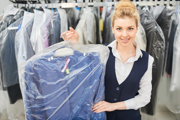 Girl Laundry worker holding a hanger Packed with clean clothes at the dry cleaners