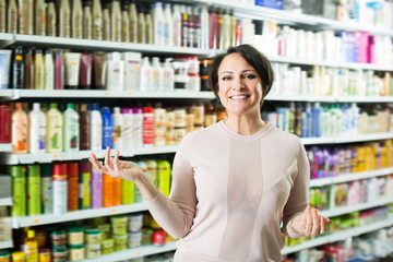 Positive woman selecting hair care products