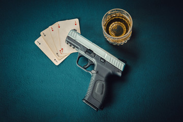 gun on four aces card and glass of scotch on poker table