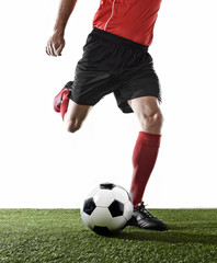 close up legs of football player in red socks and black shoes running and kicking the ball